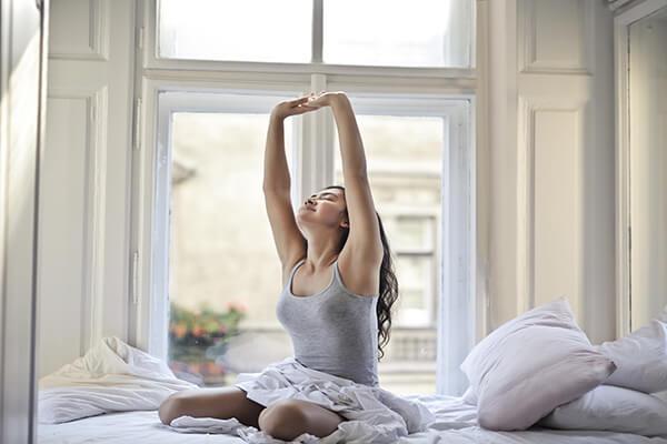 目覚めに背伸びをする女性
