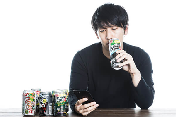 チューハイを飲みながら携帯を眺める男性