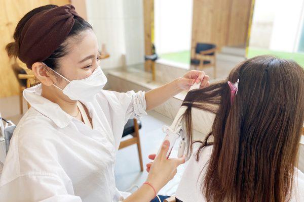 美容師が髪を巻いている様子